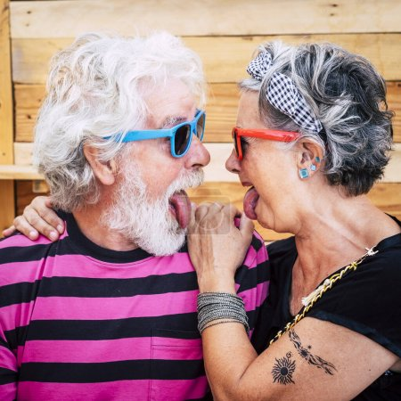 Portrait of cheerful senior crazy couple with wood...
