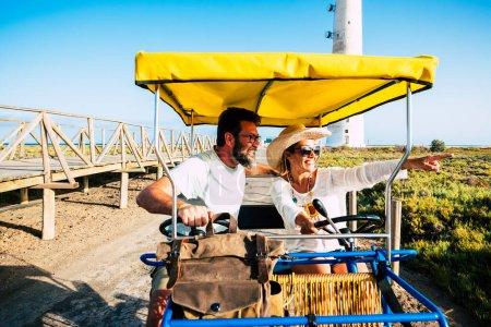 Photo pour Touristiques et touristiques concept de personnes avec un couple adulte joyeux et heureux sur un vélo surrey profiter de l'activité de loisirs de plein air - image libre de droit