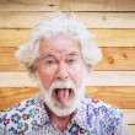 Portrait of cheerful senior crazy man with wood ba...