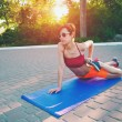 The girl is engaged in morning yoga. A woman is tr...