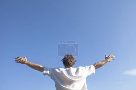 Photo pour Homme profitant du grand air - levant les bras au-dessus du ciel bleu - vue arrière - image libre de droit