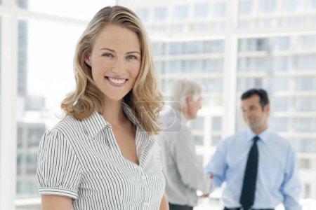 Photo pour Portrait d'une jeune femme d'affaires avec des partenaires sur fond - poignée de main avec succès des dirigeants d'entreprises - image libre de droit