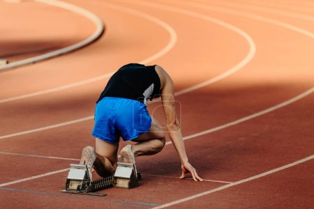 Photo for Male runner starting blocks of 400-meter sprint at competition - Royalty Free Image
