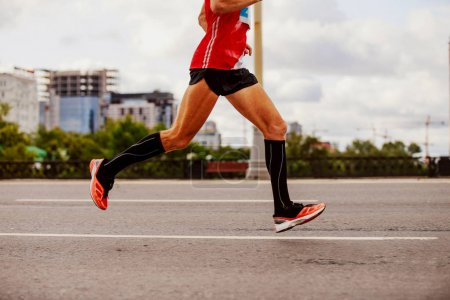 Photo for Man marathon runner in compression socks running city - Royalty Free Image