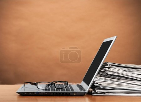 Laptop and black glasses ans stack of newspapers