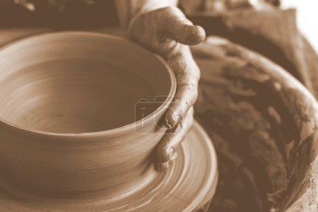 Potter making clay pot, close-up view