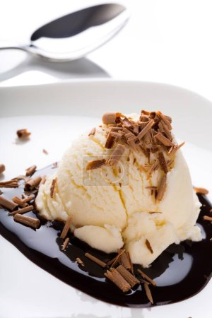 Vanilla ice cream with chocolate sauce on background
