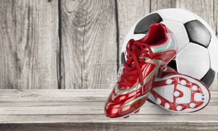 Football shoes and ball on wooden background
