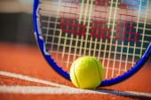 Tennis racket and ball on court background