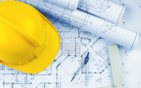 Yellow hard hat and blueprints, construction concept