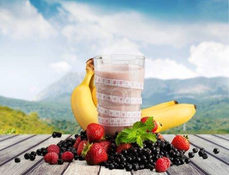 Photo for Tasty milk shake, fruity yogurt  and Measuring tape - Royalty Free Image