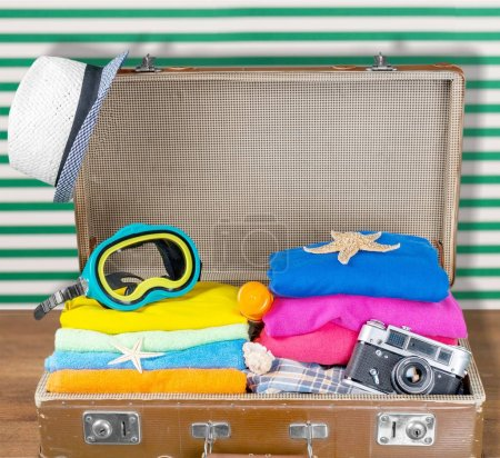 Photo for Retro suitcase with clothes and snorkeling mask. Travel and vacation - Royalty Free Image