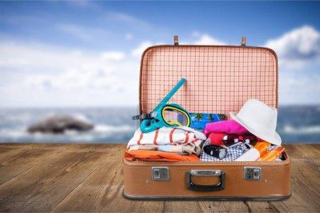 Photo pour Valise rétro avec des vêtements et masque de snorkeling. Voyage et vacances - image libre de droit