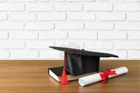 Photo for Graduation hat, book and diploma on wooden table - Royalty Free Image