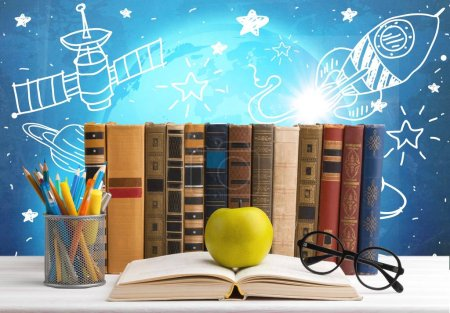 Photo for Row of books, pencils, eyeglasses, green apple on open book - Royalty Free Image