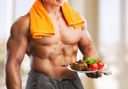 Photo for Muscular man holding plate with meat and vegetables, food for bodybuilder - Royalty Free Image