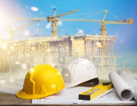 Photo for Blueprints and tools with hardhats on construction site - Royalty Free Image