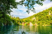 Plitvice Lakes National Park beautiful daytime landscape, green forest, waterfalls, blue cloudy sky and reflection in amazing green water of nature lake, image suitable for wallpaper or guide book