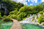 Beautiful sunny day in the Plitvice Lakes National Park, tourist route on the wooden flooring through turquoise lake, waterfall and green forest with blue cloudy sky, popular destination in Croatia