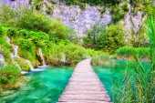 Tourist route on the wooden flooring in the famous Plitvice Lakes National Park across amazing colored water, green and waterfalls, nature background for guide book or poster