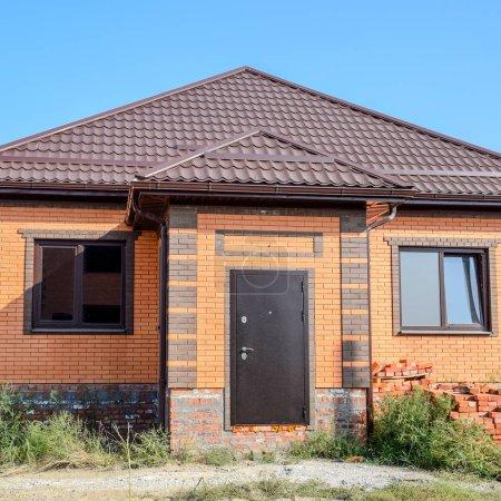 Photo pour La maison avec des fenêtres en plastique et un toit en tôle ondulée. Toiture de profil métallique ondulé sur la maison avec fenêtres en plastique . - image libre de droit