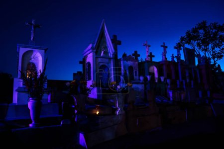 Dark blue lightened tombstones with buring candles...
