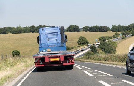 Photo pour Un camion à plat vu de l'arrière sur la route A303 dans le Wiltshire, Angleterre Royaume-Uni. Véhicule déchargé circulant sur une chaussée à voie unique très fréquentée . - image libre de droit
