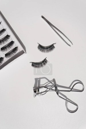 Photo for Black false lashes strips set with curler and tweezers on white - Royalty Free Image