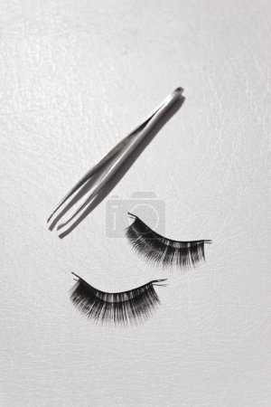 Photo for Black false lashes strips with tweezers on white background - Royalty Free Image