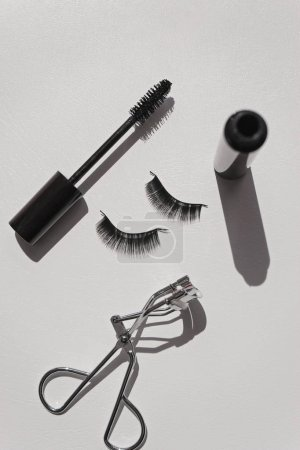 Photo for Black false lashes strips with mascara and curler on white  background - Royalty Free Image
