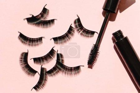 Photo for Black false lashes strips with mascara on pink background - Royalty Free Image