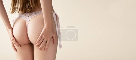 Photo for Cropped shot of woman wearing pink lingerie touching buttocks - Royalty Free Image