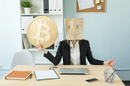 Crypto currency, virtual money and blockchain concept - Woman wearing funny paper mask with bitcoin symbol in office
