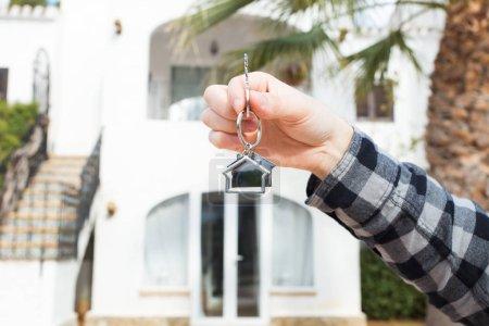 Photo pour L'immobilier et la notion de propriété - main tient les clés de la maison sur maison en forme de trousseau devant une maison neuve. - image libre de droit