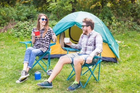 Photo for People, summer tourism and nature concept - young couple sitting near a tent. - Royalty Free Image