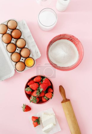 Raw ingredients for cooking strawberry pie or cake on pink background  (eggs, flour, milk, sugar, strawberry), top view, flat lay. Bakery background. Recipe for strawberry pie