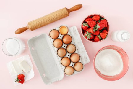 Flat lay raw ingredients for cooking strawberry pie or cake on pink background  (eggs, flour, milk, sugar, strawberry), top view. Bakery background. Recipe for strawberry pie