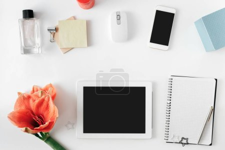 Photo for Flat lay, top view office table desk. Feminine desk workspace with flower amaryllis, tablet, notebook with pen, smartphone, computer mouse and female perfume - Royalty Free Image