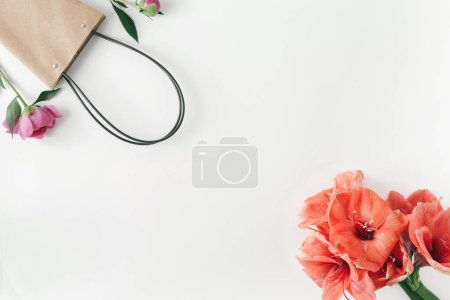 Top view of paper shopping bag with flowers amaryllis and peonies on white background