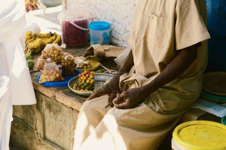 Elderly man seller selling food at African market