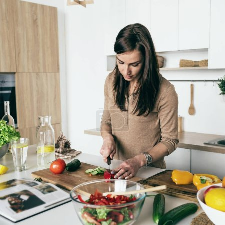 Woman cutting vegetables for summer salad at home kitchen