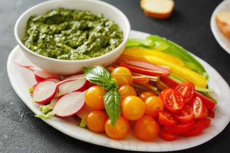 Photo for Raw vegetables snack and pesto sauce on black stone background. Vegetarian healthy food - Royalty Free Image