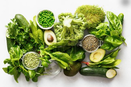 Photo for Set raw healthy food clean eating vegetables and grain products source of protein for vegetarians: cucumber, lucerne, zucchini, spinach, basil, green peas, avocado, broccoli, lime and green lentils on white concrete background, top view - Royalty Free Image
