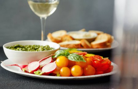 Photo for Healthy snacks for wine. Vegetables, bread croutons with pesto sauce and garlic sauce on black stone background with white wine - Royalty Free Image