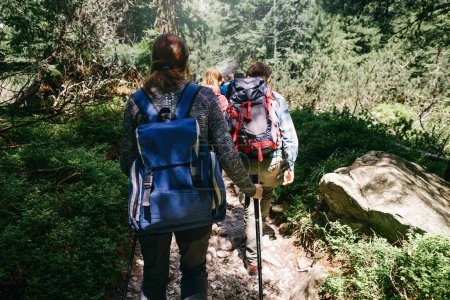 Travel and backpacking lifestyle concept. Group of travelers with backpacks hiking in forest