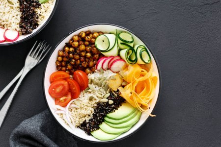 Clean and balanced healthy food concept. Two vegetarian buddha bowl. Rice, spicy chickpeas, black and white quinoa, avocado, carrot, zucchini, radish, tomatoes on dark background close up, top view
