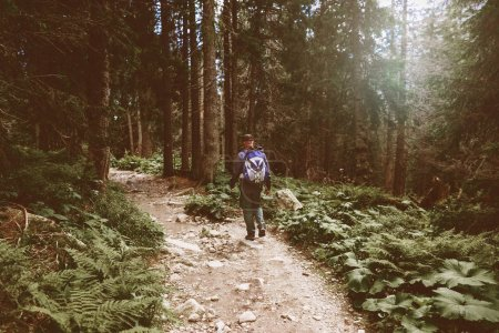 Male traveler with backpack walking dense forest. Travel and backpacking lifestyle concept