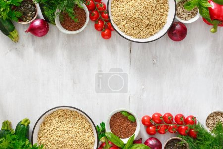 Raw healthy food background. Green buckwheat with vegetables for cooking raw food on white wooden table with copy space top view