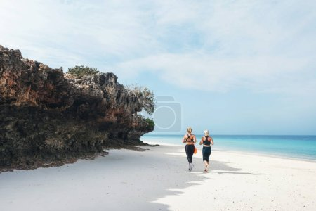 Two women runners during the morning jog along the beach. Healthy lifestyle concept. Workout