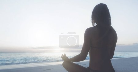 Young woman practicing yoga on beach at sunrise